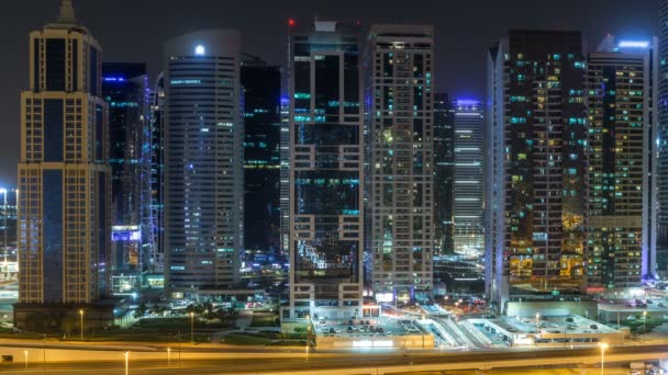 Aerial view of Jumeirah lakes towers skyscrapers during all night timelapse with traffic on sheikh zayed road.