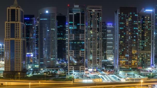 Letecký pohled na Jumeirah lakes towers mrakodrapy během všech noční timelapse s provozem na bulváru sheikh zayed road