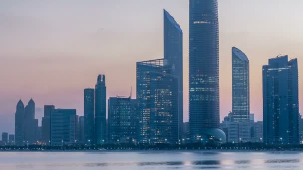 Abu Dhabi city skyline with skyscrapers before sunrise with water reflection night to day timelapse