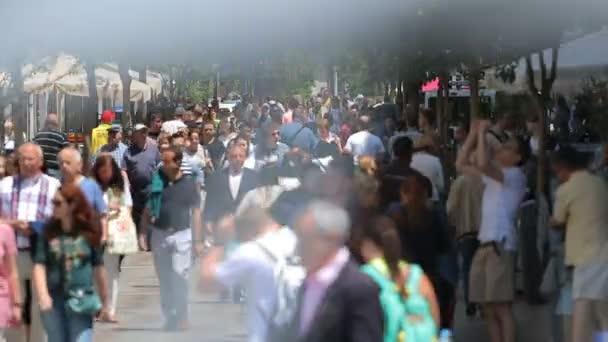 Crowd of people walking on the street in Madrid near Puerta del Sol.