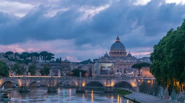 Rome, Italy: St. Peter's Basilica, Saint Angelo Bridge and Tiber River after the sunset day to night transition timelapse. View from bridge with beautiful cloudy sky