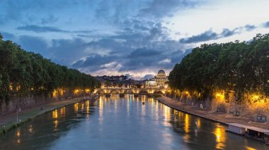 Rome, Italy: St. Peter's Basilica, Saint Angelo Bridge and Tiber River after the sunset day to night transition timelapse hyperlapse. View from bridge with beautiful cloudy sky