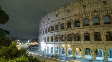 view of Colosseum illuminated at night timelapse hyperlapse in Rome, Italy. Top view. Traffic on the road