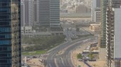Dubai öböl üzleti towers a nap idő légi timelapse. Tetőtéri nézetet felhőkarcolók és új torony építés alatt. A közúti forgalom