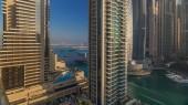 Fényképek Nézd a modern felhőkarcolók csillogó sunrise fények timelapse-Dubai Marina, Dubai, Egyesült Arab Emírségek jachtok. Sugarai fények tükröződik üveg.