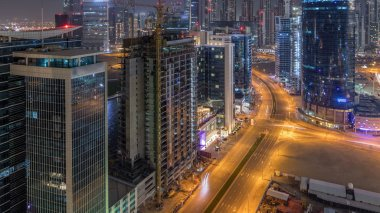 Dubai business bay towers aerial night timelapse. Rooftop view of some illuminated skyscrapers and new towers under construction. Traffic on the road