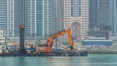 Excavator and modern skyscrapers in Dubai city at morning timelapse from the Palm Jumeirah Island. Dubai, United Arab Emirates. Construction near Dubai marina