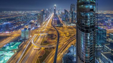 Scenic Dubai downtown skyline at night timelapse. Rooftop view of traffic on Sheikh Zayed road with numerous illuminated towers.