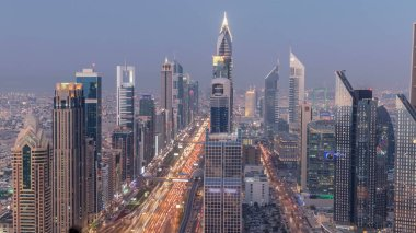 Dubai downtown skyline day to night transition timelapse. Rooftop view of traffic on Sheikh Zayed road with numerous illuminated towers.