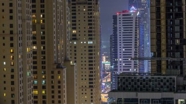 Night illumination of Dubai Marina and JBR aerial timelapse, UAE. Modern skyscrapers and residential buildings. Traffic on the road and glowing windows