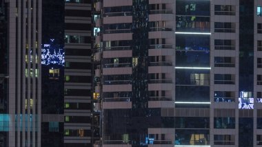 Windows of the multi-storey building of glass and steel lighting inside and moving people within timelapse. Aerial view of modern residential skyscrapers in Dubai. Pan left stock vector