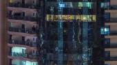 A többszintes épület, az üveg és acél, belső világítás, és mozgó emberek timelapse Windows. A légi felvétel a modern lakó- és office felhőkarcoló-ban Dubai marina. Pan le