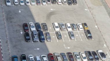 Top view of parking lot timelapse from rooftop of skyscraper, with varieties of colored vehicles such as yellow, white, black, grey, silver, blue and other. Cars changes, shadows moves fast. Dubai, UAE
