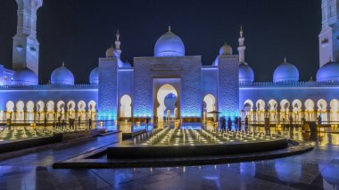 Sheikh Zayed Grand Mosque illuminated at night timelapse hyperlapse, Abu Dhabi, UAE. Front view with fountains. The 3rd largest mosque in the world