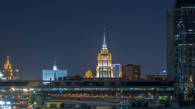 Hotel Ukraine and pedastrian bridge timelapse, landmark near historic center of Moscow. Cityscape in snowy winter evening. Panorama view on city at night.