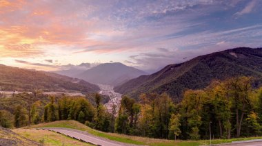 Autumn in High Mountains at sunset with dramatic clouds. Sochi, Russia. Krasnaya Polyana timelapse. View to trees with road