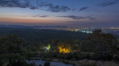 A bird's eye view before sunrise over Antalya night to day transition timelapse. Turkey. Morning mist. Traffic on the road. Green trees. Colorful sky