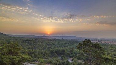 A bird's eye view of sunrise over Antalya timelapse. Turkey. Morning mist. Green trees. Colorful sky