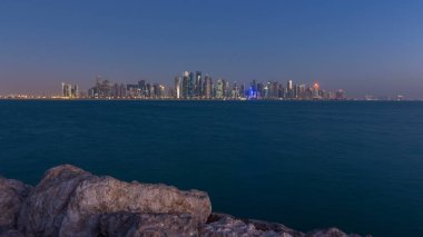 Skyline of the arabian city of Doha night to day transition timelapse in Qatar, captured in the very early morning before sunrise with illuminated skyscrapers. View from Corniche Promenade