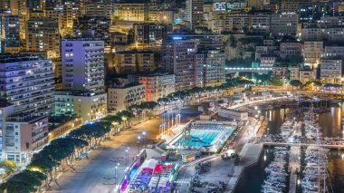 Seaside swimming pool in Monaco night timelapse, buildings in the background. Aerial top view. Traffic on the road of embankment
