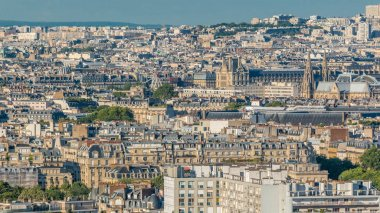 Aerial panorama above houses rooftops in a Paris timelapse. Evening view with museum and cathedral bebore sunset