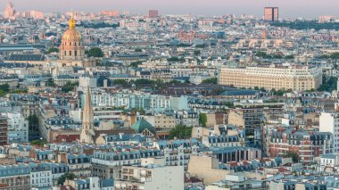 Aerial panorama above houses rooftops in a Paris day to night transition timelapse. Evening view with les invalides and other sightseeings illuminated after sunset. Zoom out