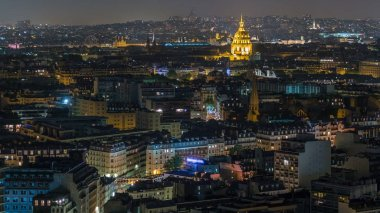 Aerial panorama above houses rooftops in a Paris night timelapse. Top view with illuminated les invalides
