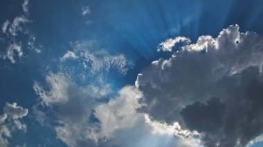 Beautiful blue sky with sunbeams and clouds timelapse. Sun rays.