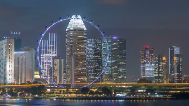 Skyline of Singapore with famous Singapore Ferries Wheel at night timelapse