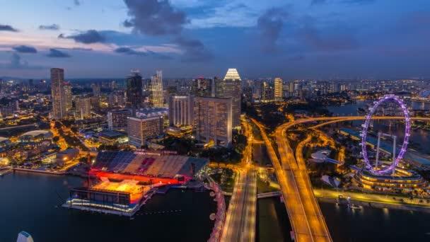 Orizzonte di Singapore con il famoso giorno di Singapore Ferries ruota a notte timelapse a penombra