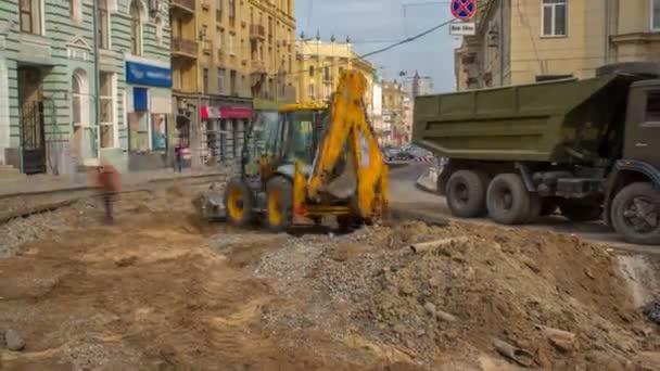 Industrieladbagger bewegt Erde und entlädt sie im Zeitraffer in einen Kipper auf der Baustelle. Luftaufnahme des Wiederaufbaus der Straßenbahngleise