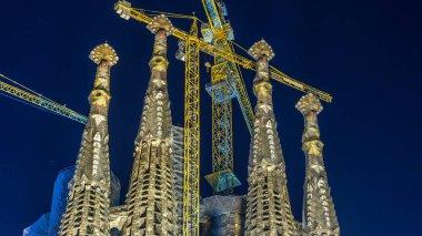 Top of Illuminated Sagrada Familia, a large Roman Catholic church in Barcelona, Spain night timelapse. Spires and cranes.
