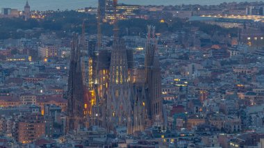Sagrada Familia, a large Roman Catholic church in Barcelona, Spain night to day timelapse. Spires and cranes. Aerial top view from bunkers at morning before sunrise