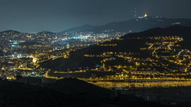 Barcelona and Badalona skyline with roofs of houses and tibidabo on the horizon night timelapse. Aerial view from Iberic Puig Castellar Village viewpoint on top of hill