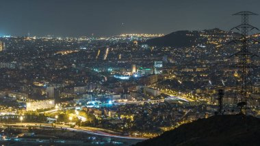 Barcelona and Badalona skyline with roofs of houses and sea on the horizon night timelapse. Aerial view from Iberic Puig Castellar Village viewpoint on top of hill