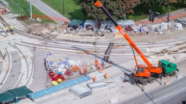 Installing concrete plates by crane at road construction site timelapse.