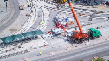 Unloading and installing concrete plates from truck by crane at road construction site timelapse. Industrial workers with hardhats and uniform. Aerial top view. Reconstruction of tram tracks on intersection stock vector