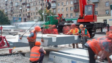 Installing concrete plates by crane at road construction site timelapse. Industrial workers with hardhats and uniform. Reconstruction of tram tracks on intersection stock vector