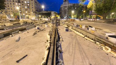Tram rails at the final stage of their installation and integration into concrete plates on the road night timelapse hyperlapse. Filling by liquid resin for reduction of vibration and noice. The process of reconstruction of tram tracks
