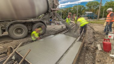 Concrete works for road construction with many workers and mixer timelapse hyperlapse. Pouring mortar to metal reinforcement. Reconstruction of tram tracks