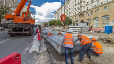 Installing concrete plates by crane at road construction site timelapse hyperlapse. Industrial workers with hardhats and uniform. Reconstruction of tram tracks in the city street stock vector