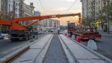 Orange construction telescopic mobile crane unloading tram rails from truck timelapse. Industrial workers with hardhats and uniform. Reconstruction of tram tracks in the city street stock vector