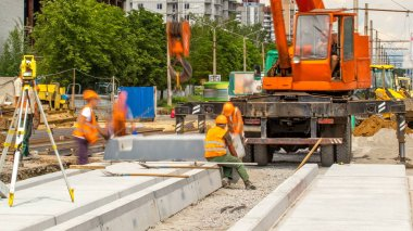 Installing concrete plates by crane at road construction site timelapse. Industrial workers with hardhats and uniform. Reconstruction of tram tracks in the city street stock vector
