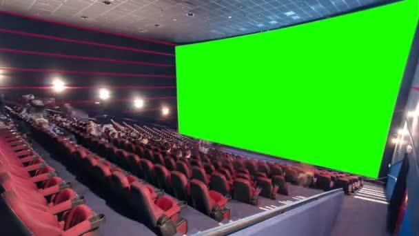 Mozi film színház nézőtér nézők, piros székek, zöld előrejelzés képernyőn timelapse