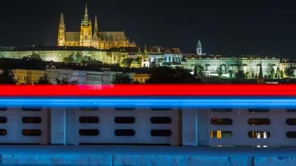 Pražský hrad v noci osvětlená přes řeku Vltava Vltavy s dopravní trasy timelapse