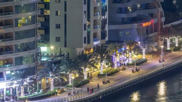 Letecký pohled na Dubai Marina z pozorovatelny noční timelapse. Lidí, kteří jdou na promenádě na nábřeží. Moderní mrakodrapy a obytné věže osvětleny s zářící okna