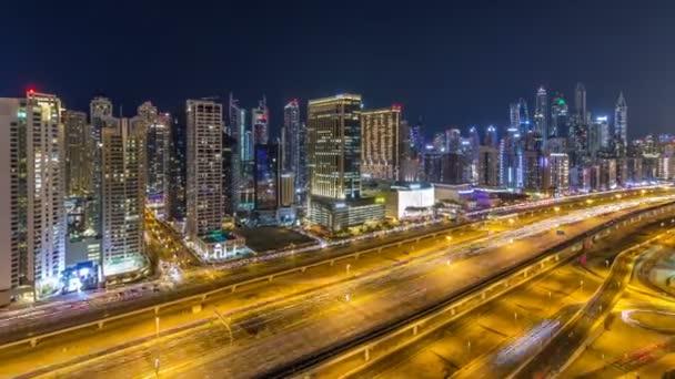 Úžasné obrovské mrakodrapy Dubaj marina timelapse. Osvětlenými mrakodrapy velkoměsta v noci, Spojené arabské emiráty. Letecký pohled od Jlt s provozem na bulváru sheikh zayed road