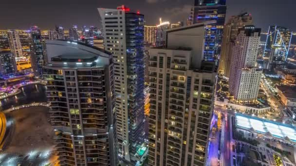 Aerial view of modern illuminated skyscrapers at Jumeirah Beach Residence JBR and Dubai marina night timelapse in Dubai, UAE