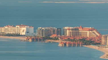 Aerial view of Palm Jumeirah Island timelapse. Evening top view with villas, hotels and yachts. World islands on a background
