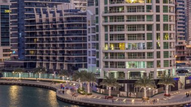 Luxury Dubai Marina canal with passing boats and promenade with palms day to night transition timelapse, Top view from above at evening after sunset. Dubai, United Arab Emirates
